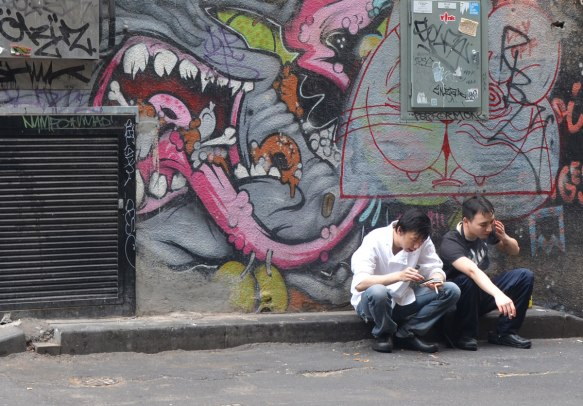 two young men sitting on a kerb smoking, they're sitting under a street art painting of a large mouth with a long tongue