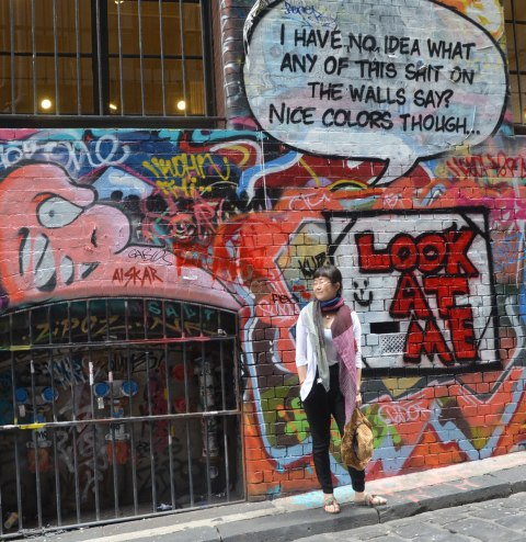 An Asian woman poses in front of a wall of graffiti. On the wall in large red letters are the words 'look at me'