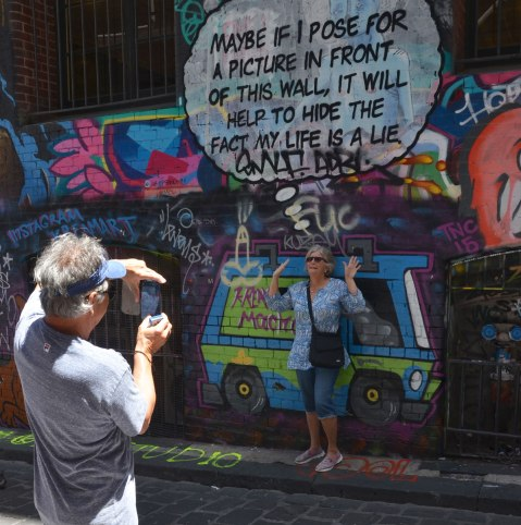 """Lots of graffiti on the wall of Hosier Lane, windows with metal bars over them, a woman poses in front of words that say """"Maybe if I pose for a picture in front of this wall it will help to hide the fact that my life is a lie"""" while a man takes her picture with a smartphone camera"""