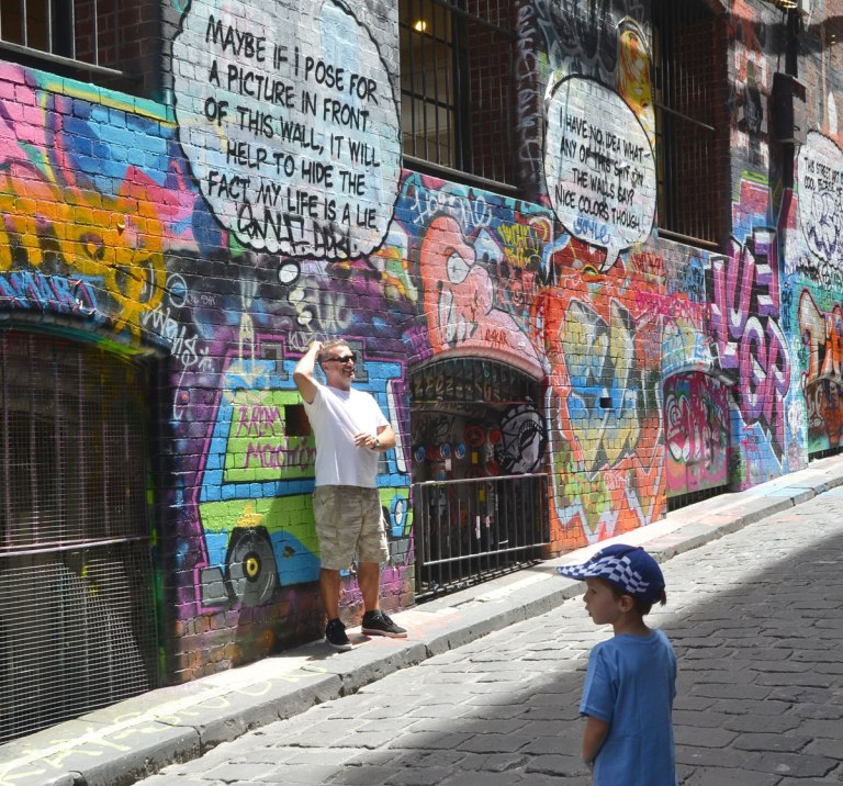 "Lots of graffiti on the wall of Hosier Lane, windows with metal bars over them, a man poses in front of words that say ""Maybe if I pose for a picture in front of this wall it will help to hide the fact that my life is a lie"""