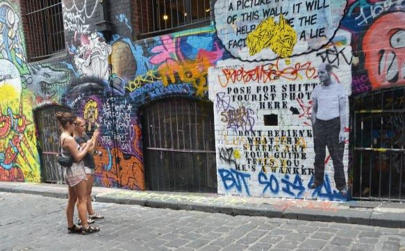 "Two women with cameras stand in front of lots of graffiti on the wall of Hosier Lane, windows with metal bars over them, including words that say ""Maybe if I pose for a picture in front of this wall it will help to hide the fact that my life is a lie"" Under those words, a large square section of the wall has been painted white and more words added: ""Pose for shitty tourist photo here"" with a black arrow pointing the place where you should stand. A life size wheatpaste picture of a man is now beside the words, where the arrow is."