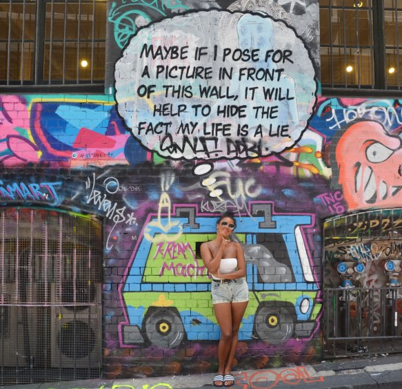 "Lots of graffiti on the wall of Hosier Lane, windows with metal bars over them, a woman poses in front of words that say ""Maybe if I pose for a picture in front of this wall it will help to hide the fact that my life is a lie"""