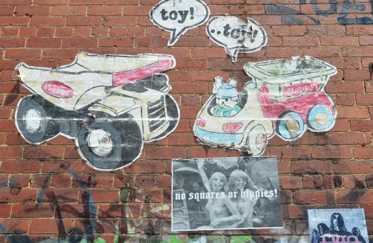 wheatpaste graffiti on a wall. A toy dump truck and a toy truck with a toy rabbut driving it. A poster of two topless women with the words not squares or hippies