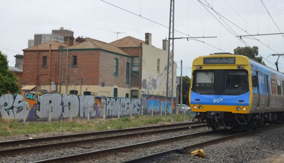 Melbourne PT train on train tracks as it passes by a wall of graffiti and some buildings behind the wall