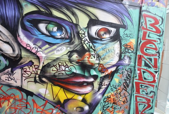 a multi coloured face painting in an alley that has had stickers added to it. The word beside the face is blender