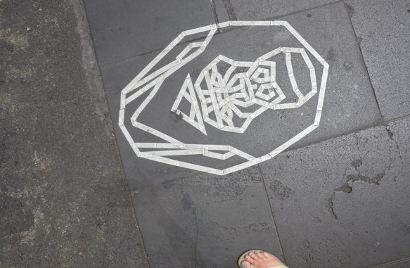 white sticky tape face-like creation on the pavement