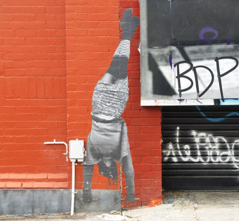 streetart paper wheatpaste black and white life sized photo of person standing on their hands on an orange brick wall
