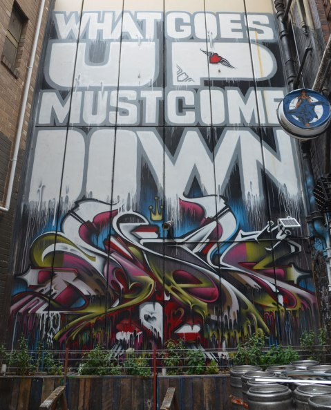 a large vertical mural at the end of an alley, with words written large that say What goes up must come down. Below the words is a swirly tag in red, white, and green