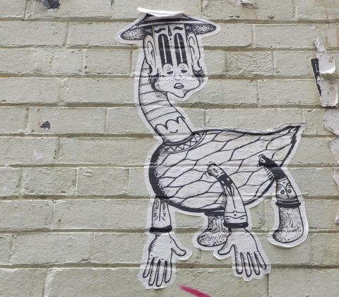 wheatpaste on a brick wall of a creature that looks like a goose with two arms and a face that is wrong