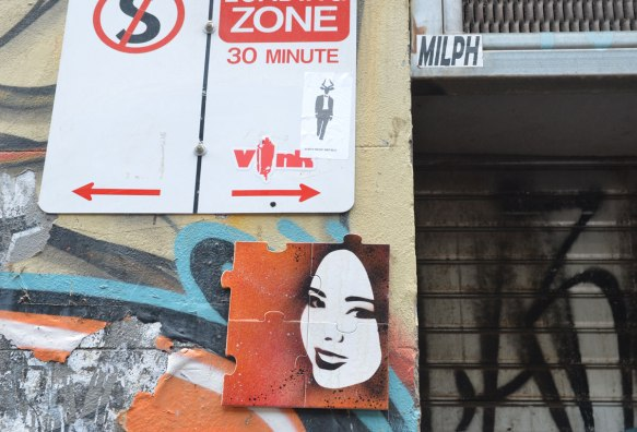 A small picture of a woman's face on a four piece puzzle on a wall in an alley, under a no parking sign