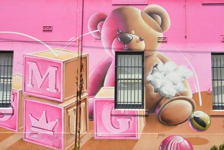 part of a larger mural - a teddy bear sitting behind three wooden blocks.  Some of the stuffing is coming out of the bear and one of his eyes has popped out.