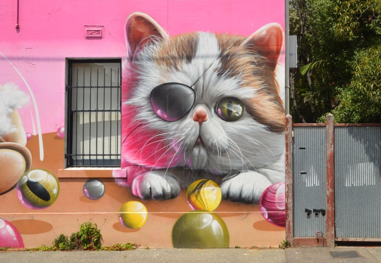 part of larger mural by smug in Melbourne, a kitten with an eye patch, standing in front of a table with marbles on it.