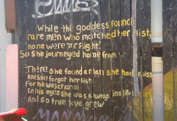 A poem written in yellow on an old wood fence