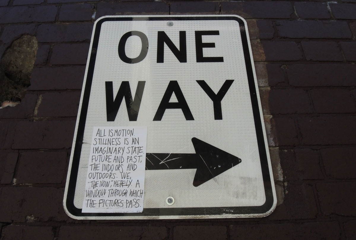 sticker on a one way sign, black words on white. All is motion. Stillness is an imaginary state, future and past, the indoors and outdoors. We 'the now' merely a window through the pictures pass