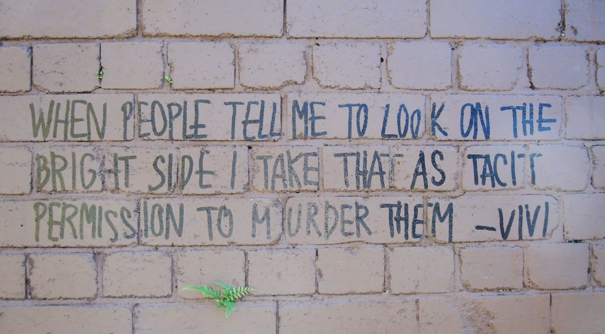 """words written in block letters, black marker on brick wall """"When people tell me to look on the bright side I take that as a tacit permission to murder them. Vivi"""""""