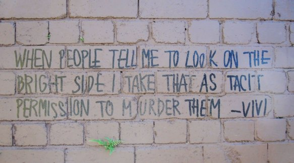 "words written in block letters, black marker on brick wall ""When people tell me to look on the bright side I take that as a tacit permission to murder them. Vivi"""