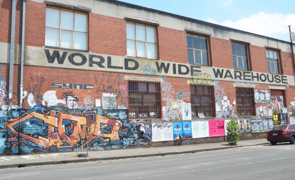 The side of World Wide Warehouse, a two storey brick bulding that is quite long. The lower level is cover with graffiti and street art except where the windows are