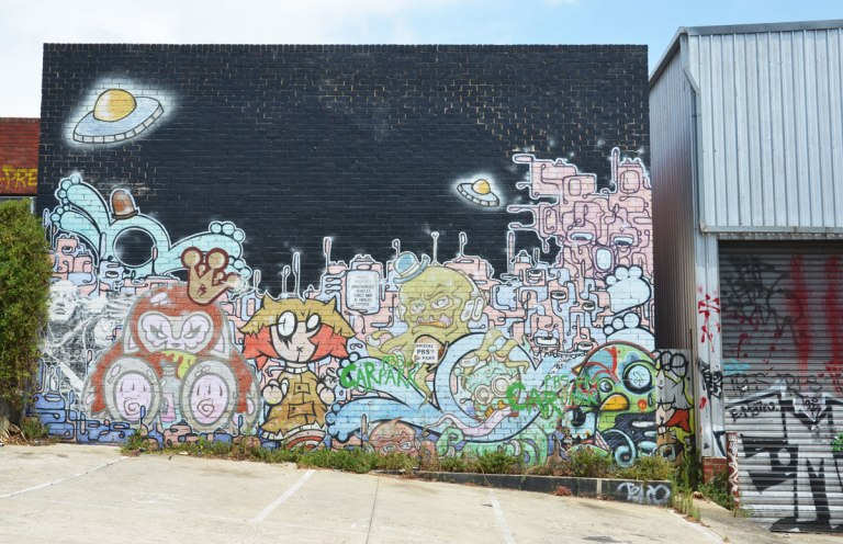 mural on a wall, the top is black sky, the bottom is a scene of people, a city and 2 flying saucers or UFO's. Not realistic looking, cartoonish