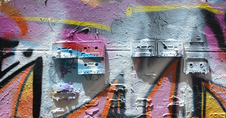 5 old cassette tapes are mounted on a wall and then covered with spray paint as part of a street art piece in Melbourne