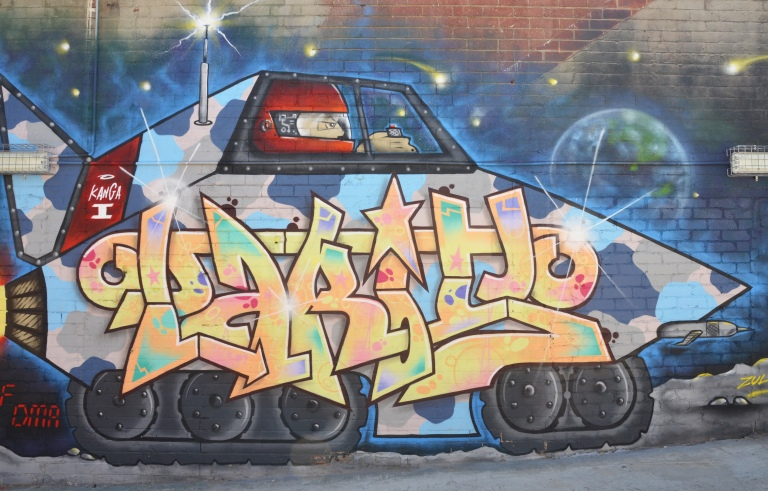 Street art painting of text within a large armed vehicle, large black tires