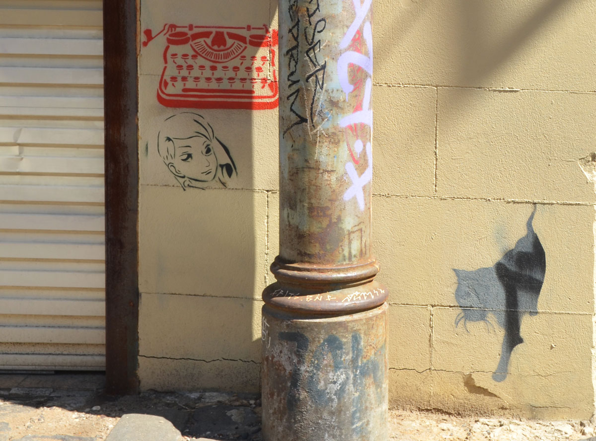 close up of metal pole in front of a wall that has three small stencils on it, a red typewriter, a woman's face and a grey and black cat, in Bach Lane, an alley in Fitzroy