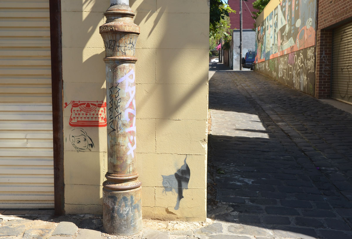 metal pole in front of a wall that has three small stencils on it, a red typewriter, a woman's face and a grey and black cat, in Bach Lane, an alley in Fitzroy