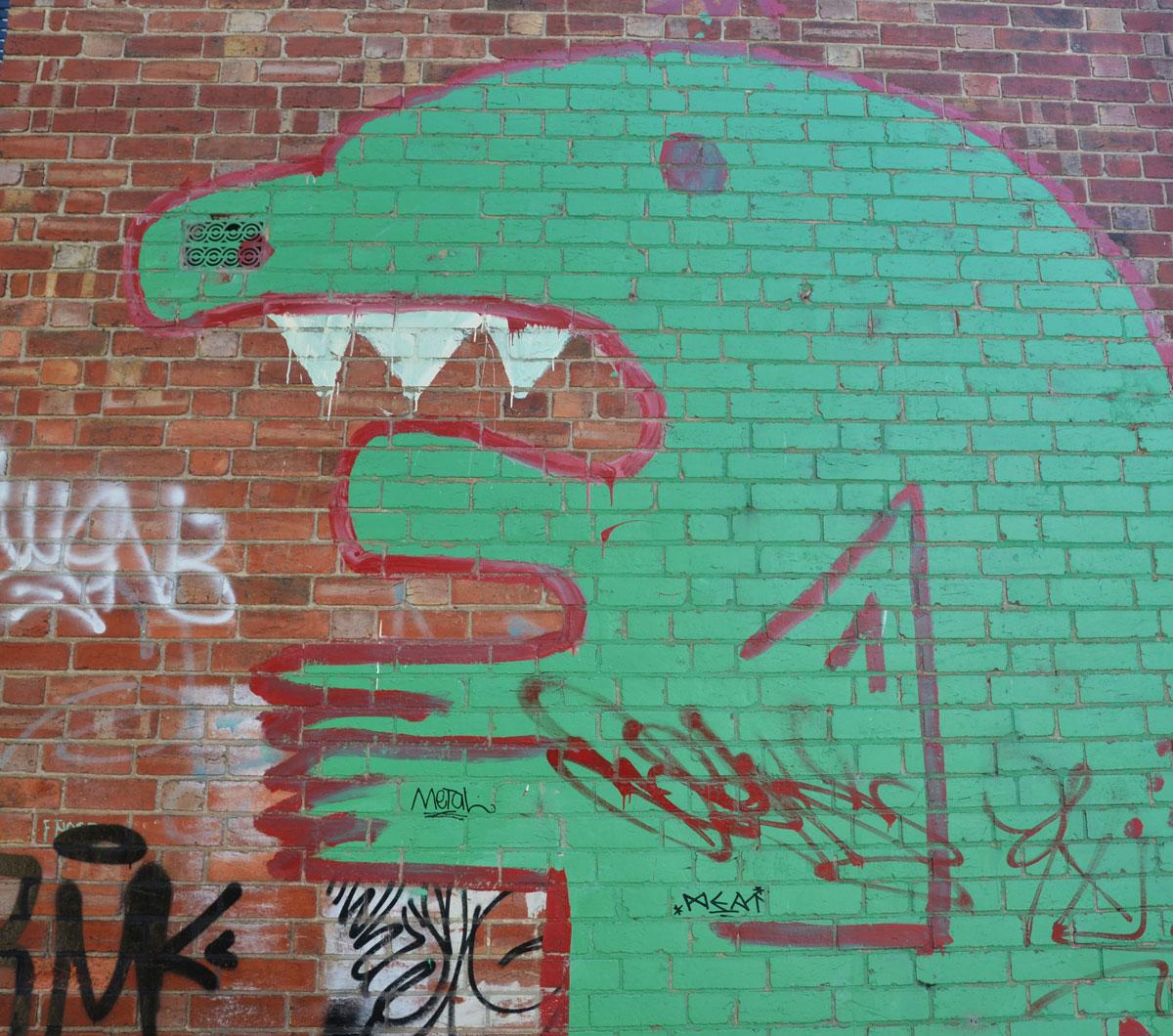 green monster street art painting on a brick wall