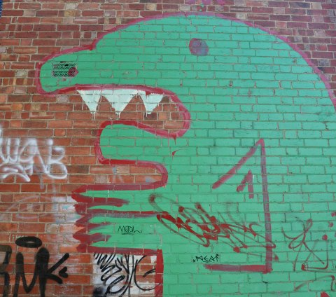 green monster street art painting on a brick wall