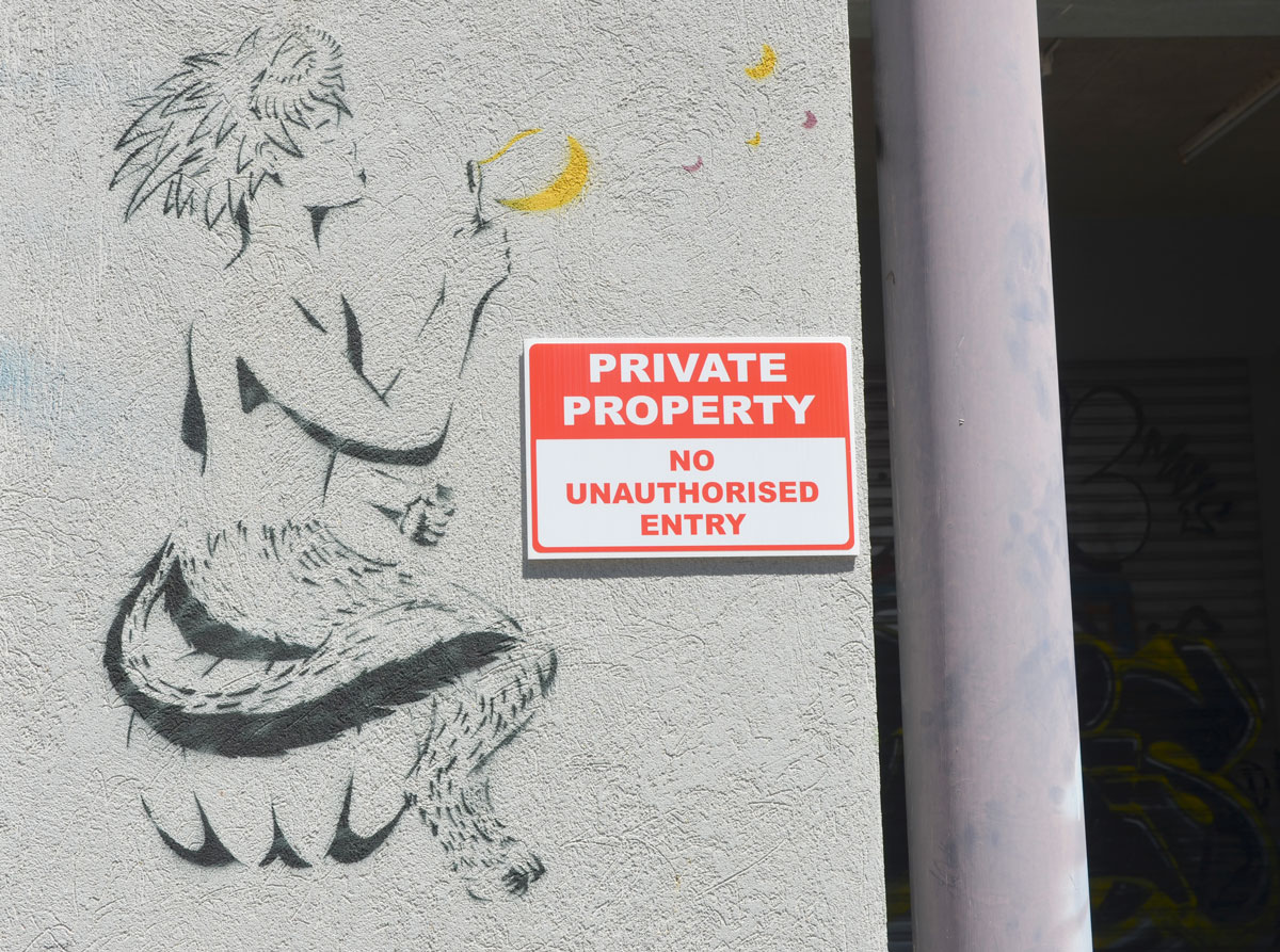 a black stencil on grey wall of a creature blowing bubbles. The bubbles have been painted yellow. The vreature is sitting. Has the upper body and arms of a human, but the legs of a hairy animal (cat? dog?).