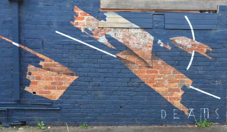 mural by deams in melbourne, negative space, wall has been painted blue except for patches where the original brick is left unpainted. close up