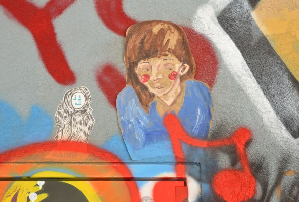 Two small paste ups. on the right is the head and shoulders of a girl with brown hair and blue top and on the left is a small black and white drawing of a little creature onto which someone has drawn blue eyes and mouth