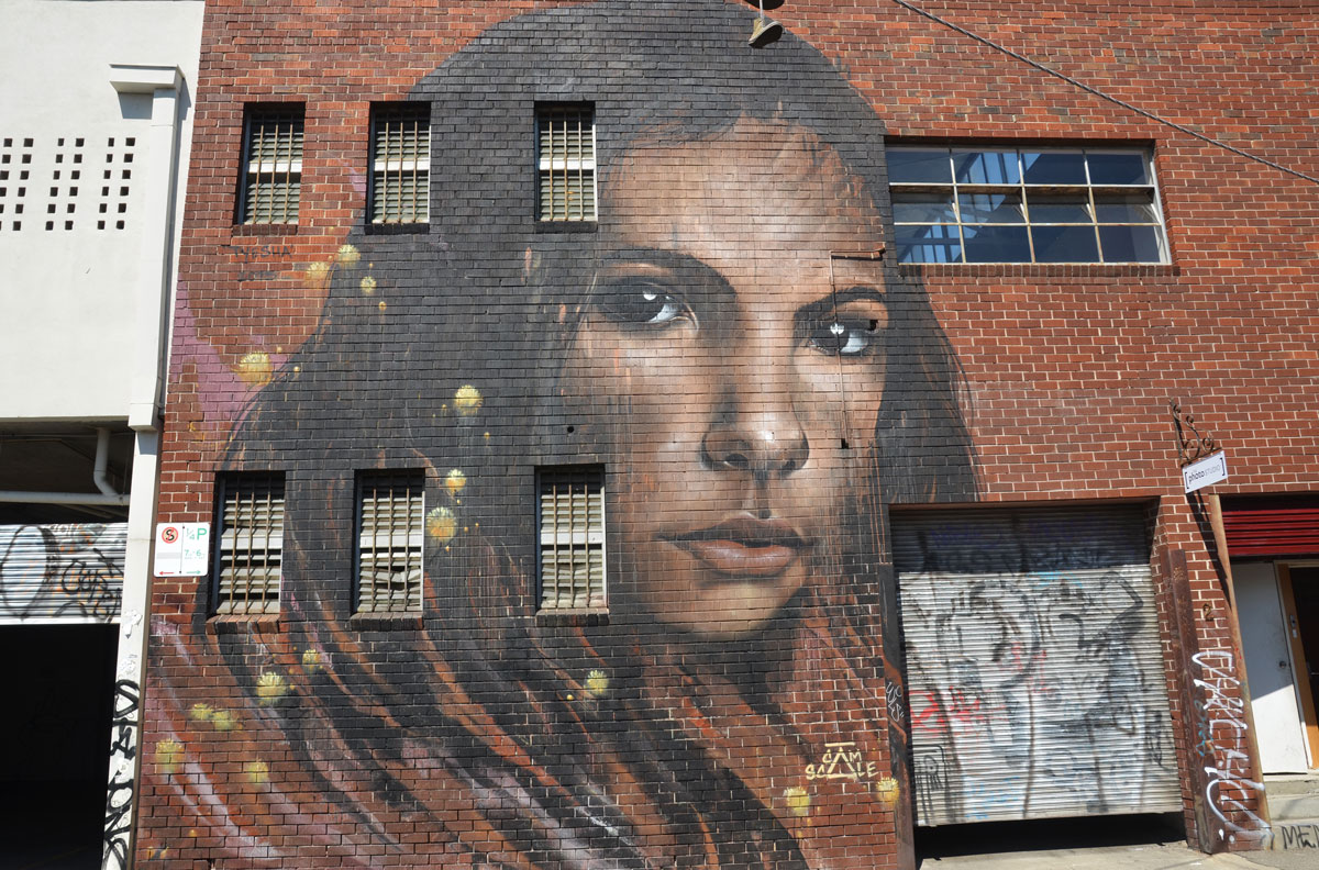 large two storey mural on a red brick building, by Cam Scale, of a woman's head and face, long black hair.