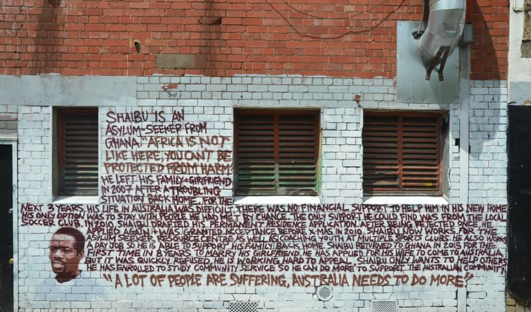 A lot of words written on a wall. Brown letters, white brick wall.