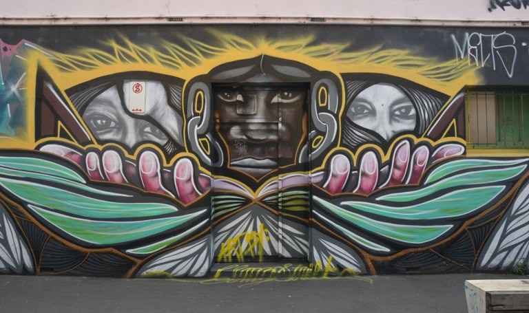A horizontal mural on a wall with a door in the middle. A brown face on the door with two hands branching from it, each hand it holding a face.
