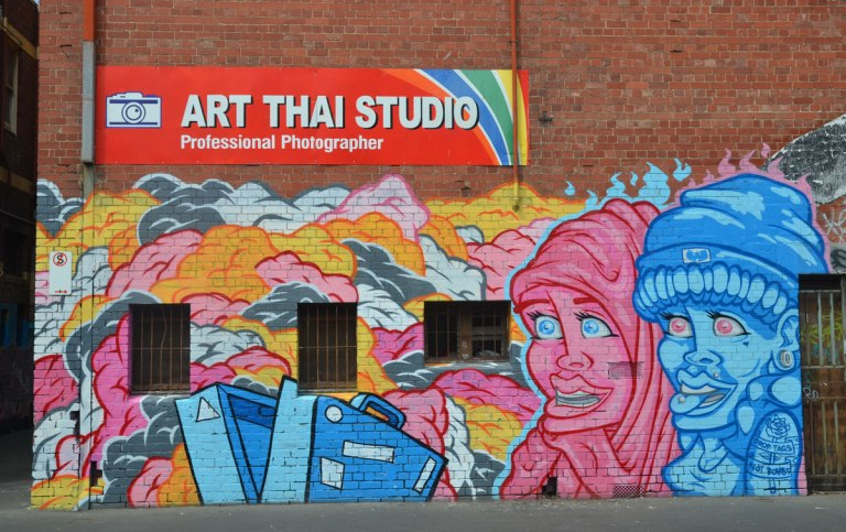 a mural featuring a pink person in head carf and a blue person