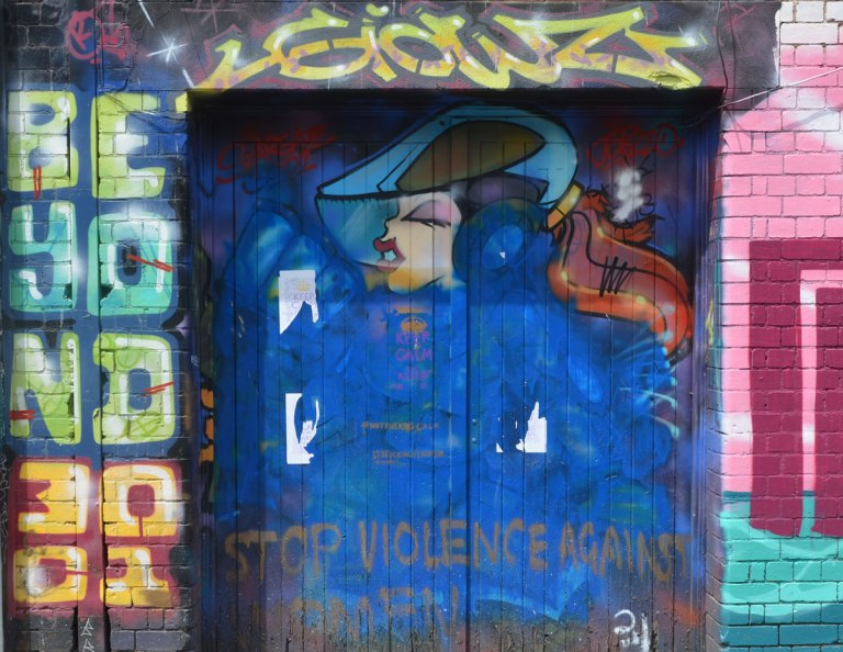 Stop Violence against women mural on a blue door