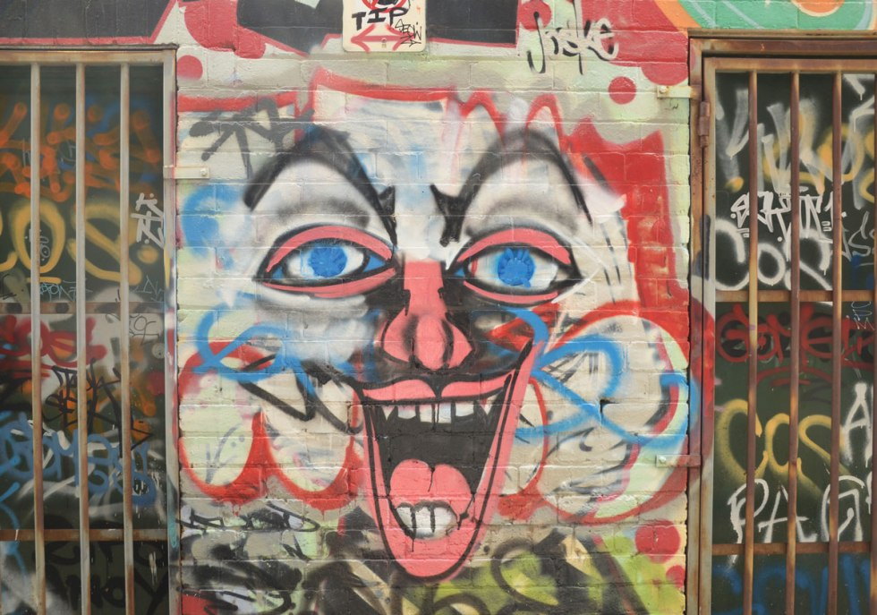 large clown like face painted on a wall between windows with metal bars. big laughing mouth and white face