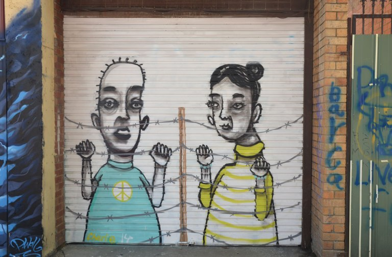 street art painting on a metal garage door of a couple standing behind a barbed wire fence