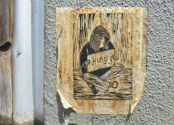 paste up of a drawing of a homeless man sitting on the sidewalk holding a sign that says hungry. printed on a book of postcodes