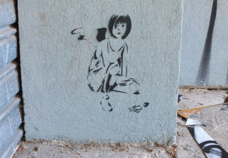 black stencil of a girl sitting on the ground with a doll on the floor beside her