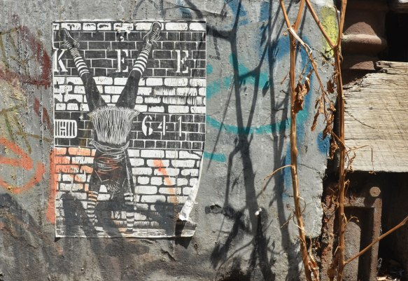 paste up of woman doing a hand stand in front of a brick wall, done in black and white