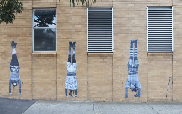 street art paste ups of three people standing on their hands, with a cane to the right of them.