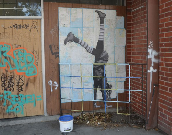 paste up by Larissa McFarlane of a life sized person doing a handstand while wearing striped socks