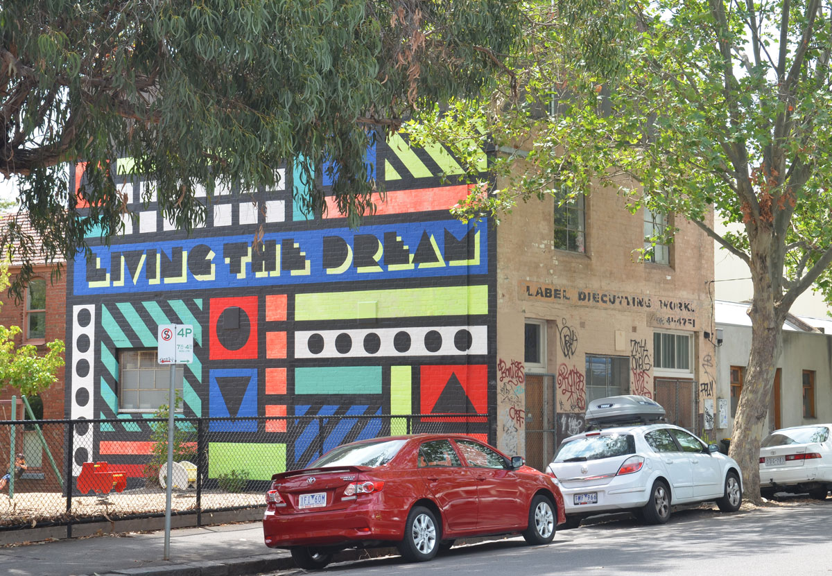 a mural of many geometric shapes on the side of a building, also with the words living the dream