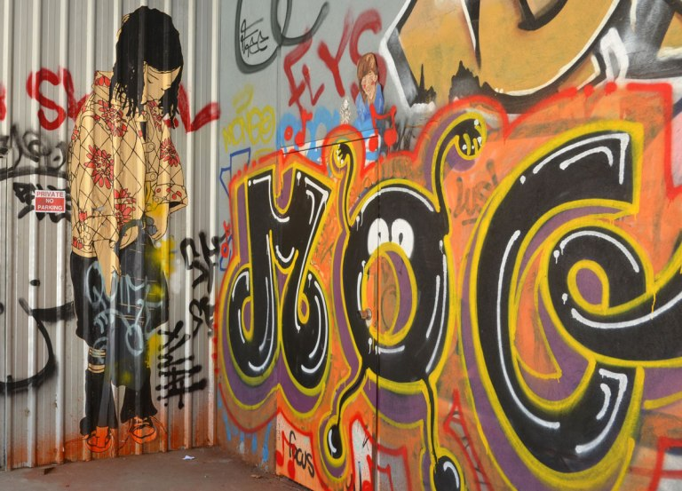 Paste up of almost life sized Asian girl standing in a corner of a garage. Short straight black hair, black pants, and a red floral print on yellow top. Beside her is a large tag graffiti with M O G. The O has been turned into the face of a little creature with big white eyes and a funny round nose