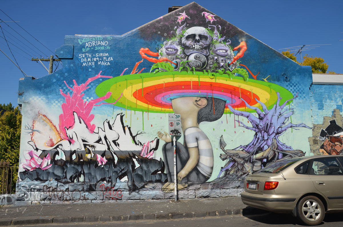mural on Rochester steet in Fitzroy, boy sitting on ground with his head looking up and into a circular rainbow. Above him is a scene with skulls