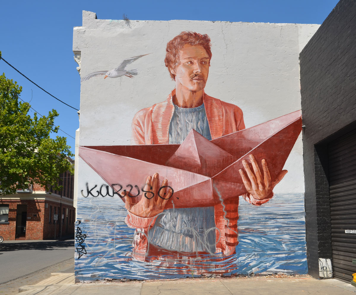 large mural of a man standing waist deep in water holding onto a folded paper boat in both hands. A seagull is flying past. The man is fully clothed.