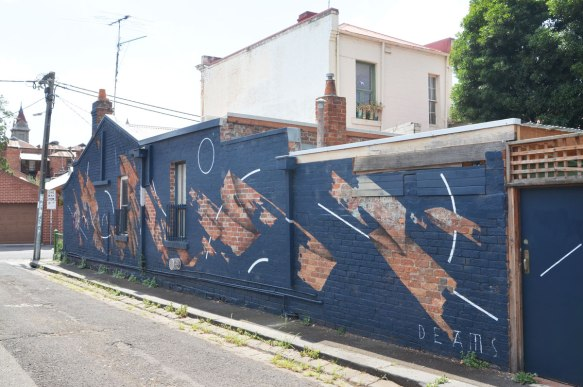 mural by deams in melbourne, negative space, wall has been painted blue except for patches where the original brick is left unpainted.