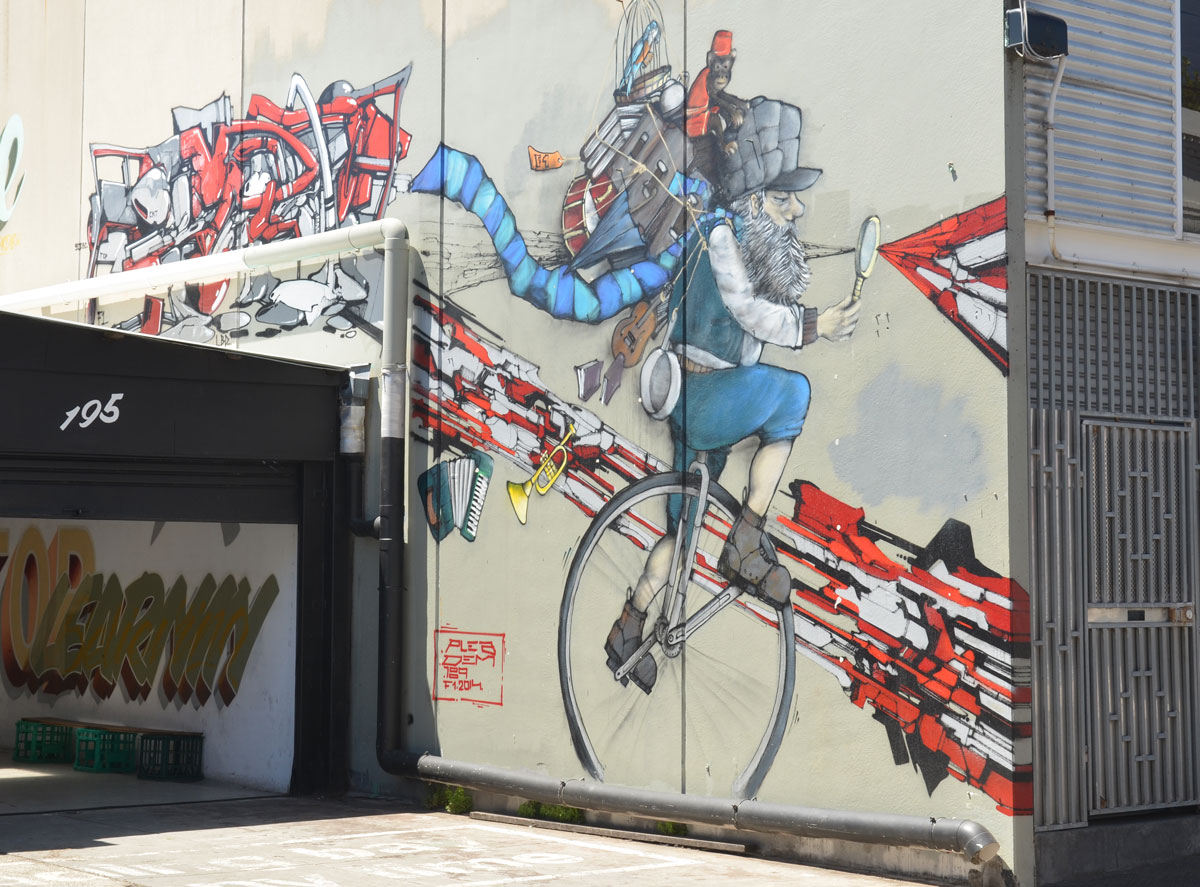 large mural by Plea and DEM 189, of an older man on a unicycle with many things on his back including a monkey and a parrot in a cage