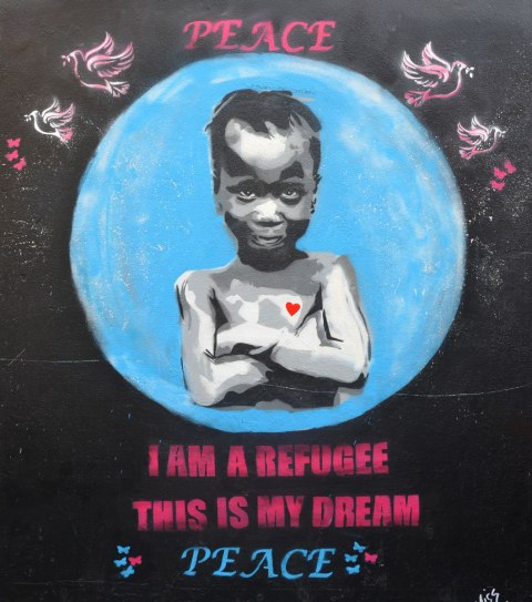 "street art painting of a child with her amrs crossed, a smile on her face, and a red heart on her chest. Words ""I am a refugee this is my dream. Peace"""